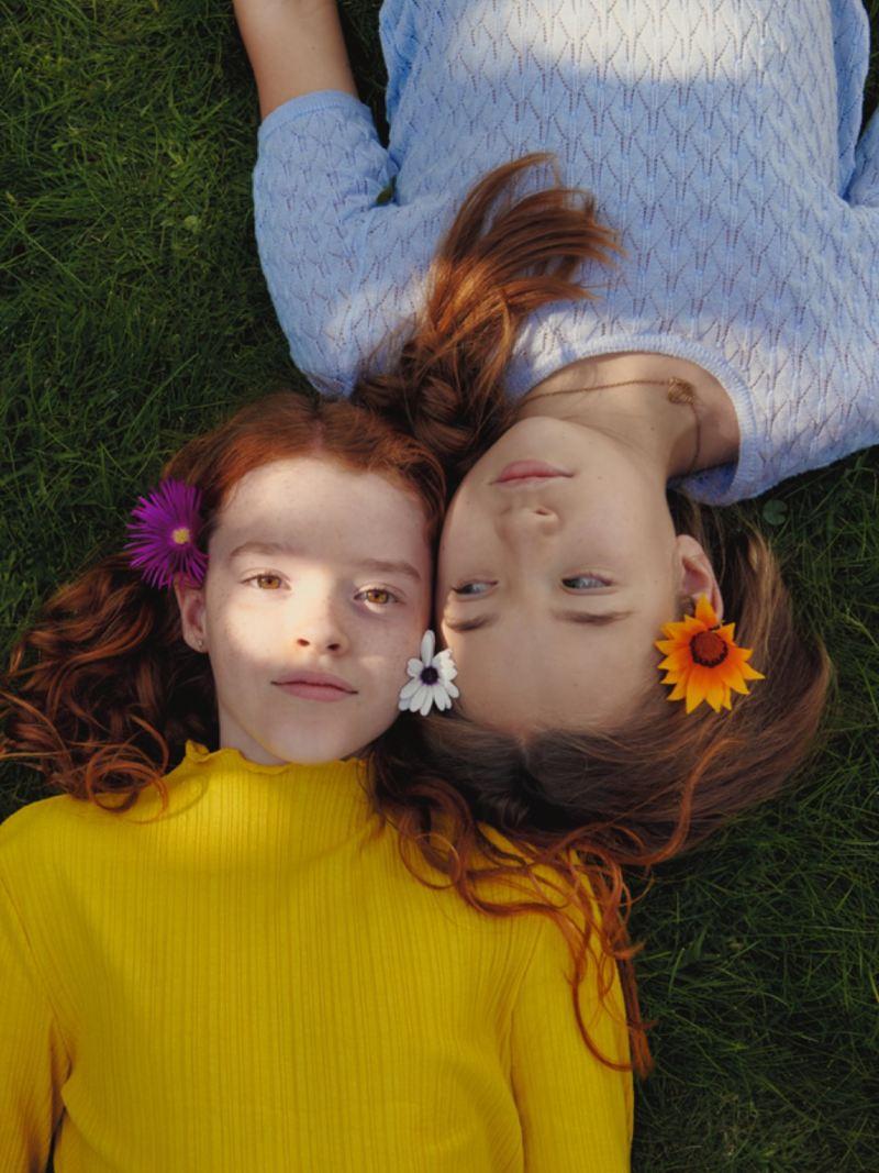Dos niñas recostadas en el césped vistas desde arriba con flores en el pelo