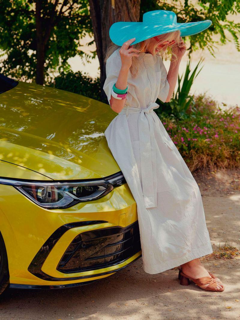 Mujer con sombrero calipso y vestido blanco apoyada en un Golf 8 amarillo aparcado debajo de unos árboles