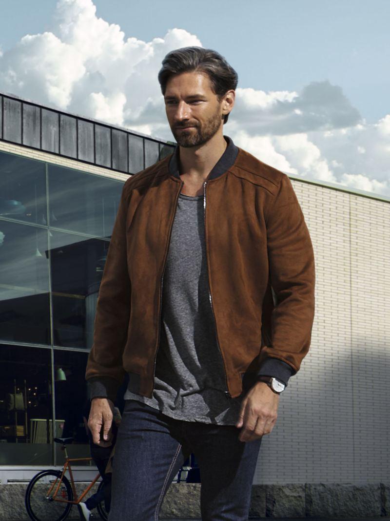 Hombre con una chaqueta marrón caminando a la luz del día