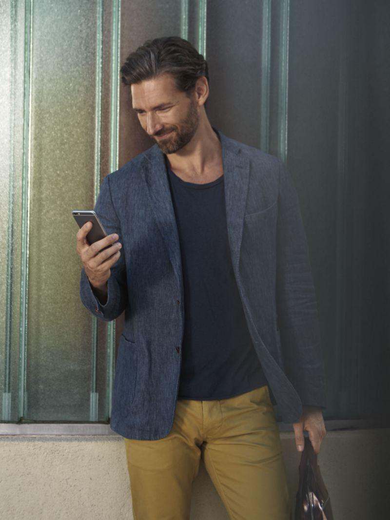 Hombre sonriente mientras mira la pantalla de su móvil