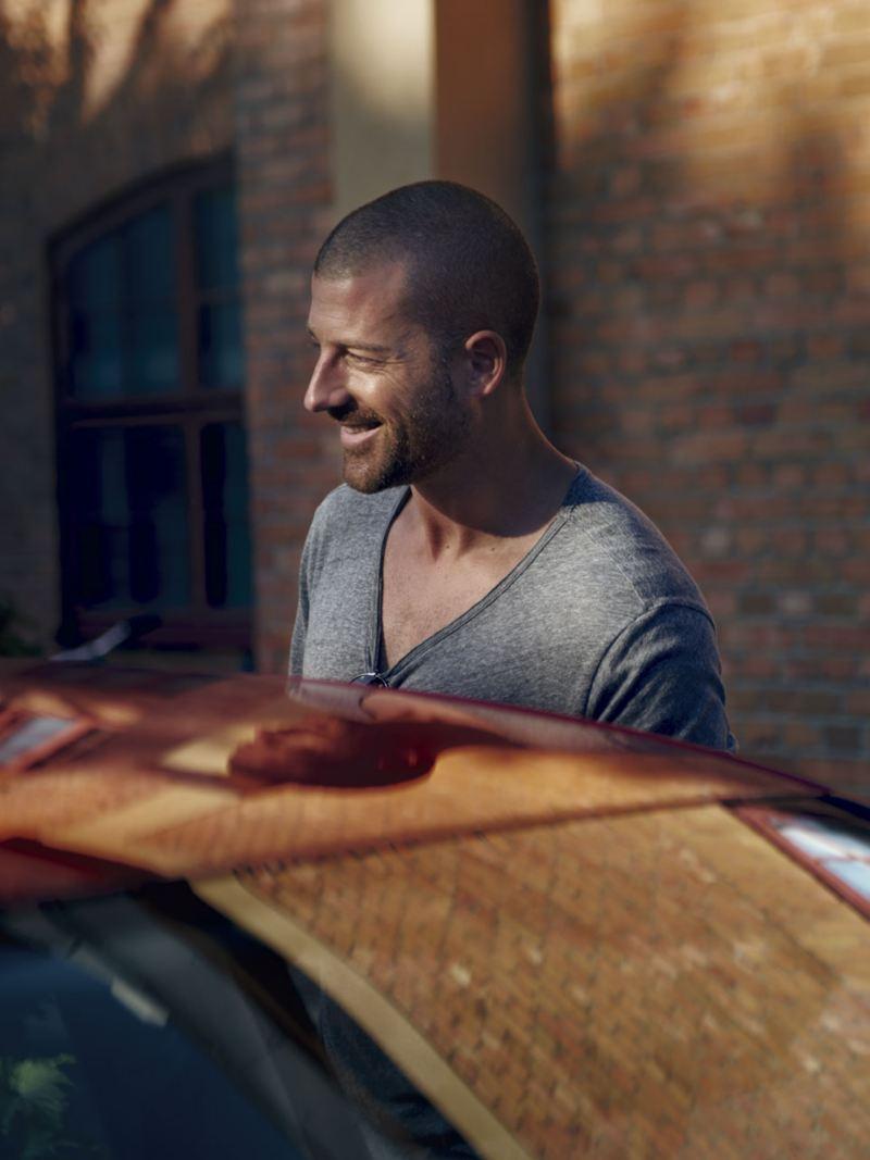 Hombre con el pelo corto sonriente mientras entra en un Golf GTI
