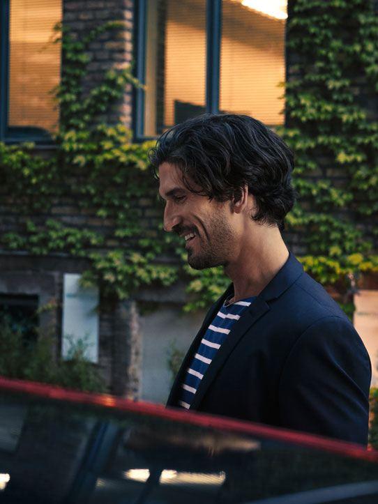 Hombre sonriente junto a un Golf Sportsvan rojo frente a una casa con pared ajardianada