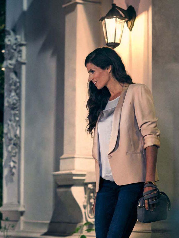 Chica joven con una chaqueta beige saliendo de una casa por la noche