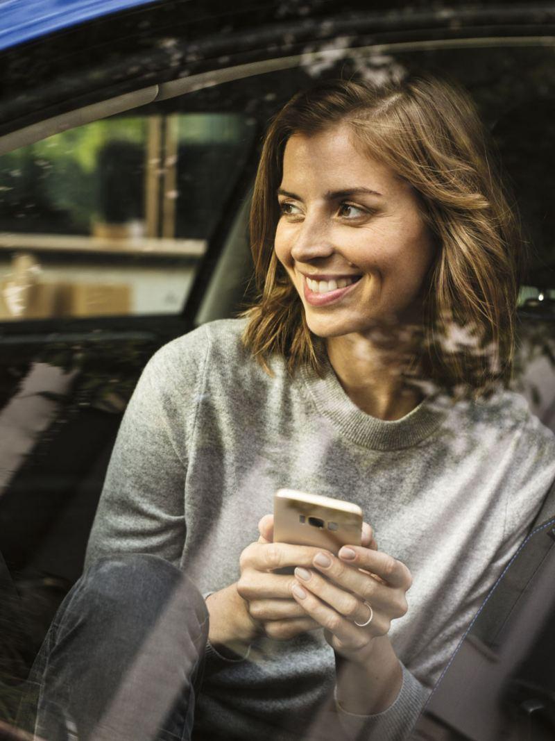 Chica sonriente con un móvil en la mano sentada en el asiento del conductor de un Golf Variant azul