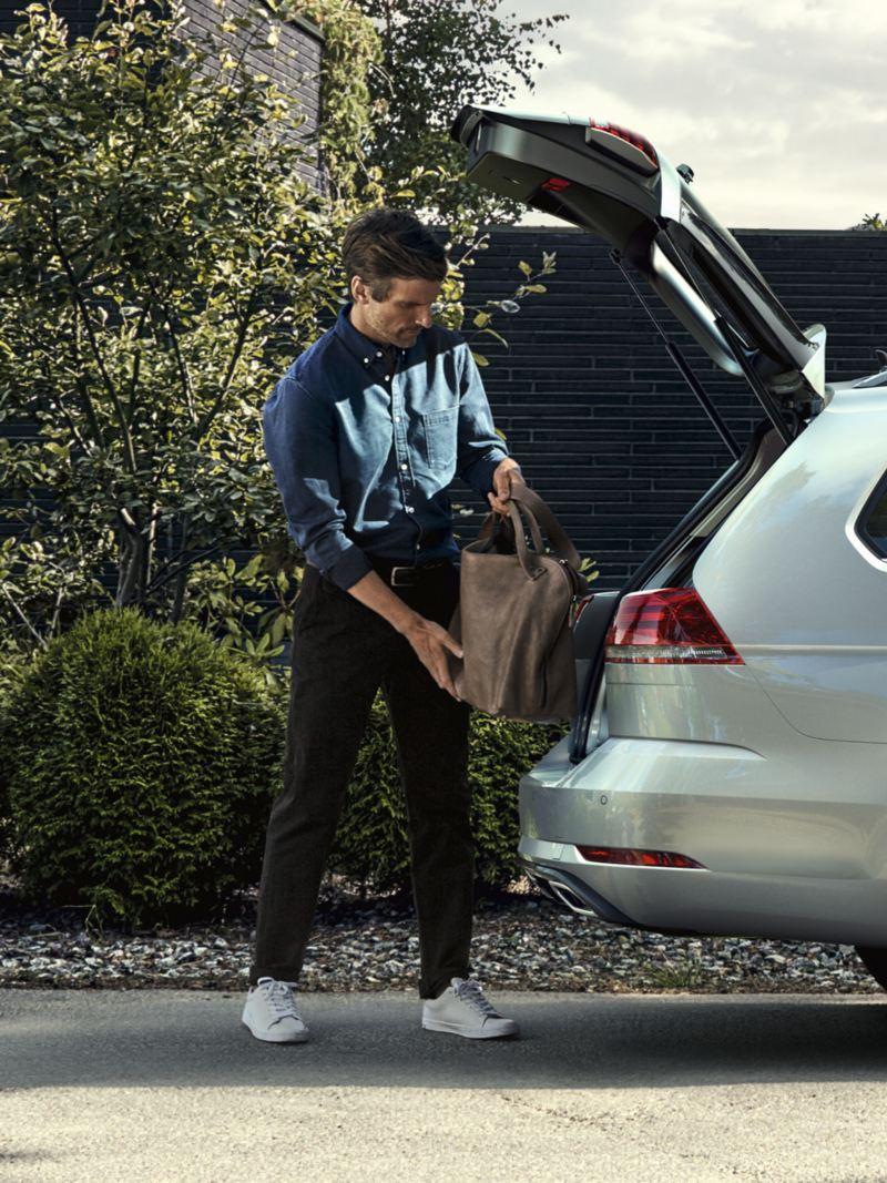 Hombre guardando una bolsa en el maletero de un Golf Variant plateado