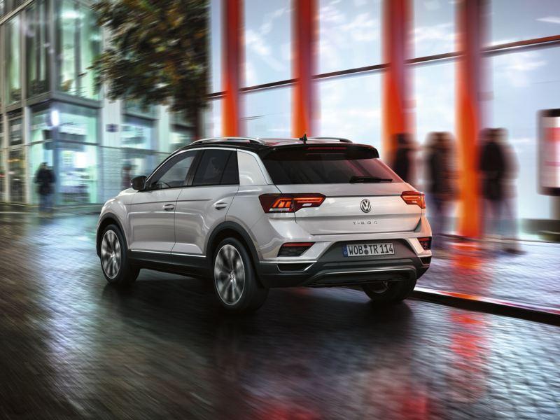 Volkswagen T-Roc blanco visto desde atrás circulando por la ciudad de noche