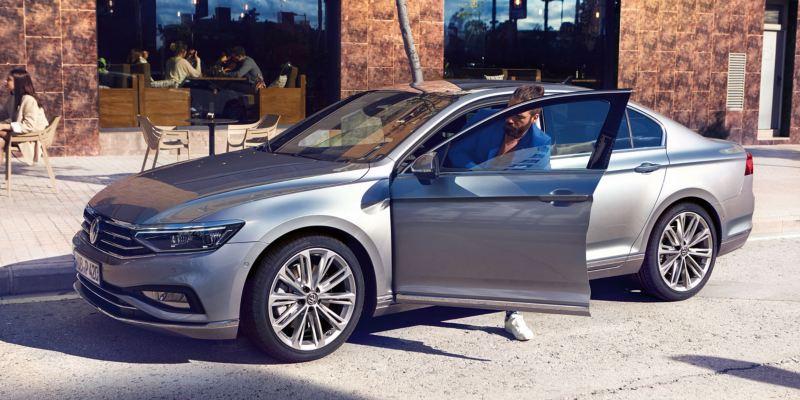 Hombre bajando del un Volkswagen Passat gris aparcado en la calle