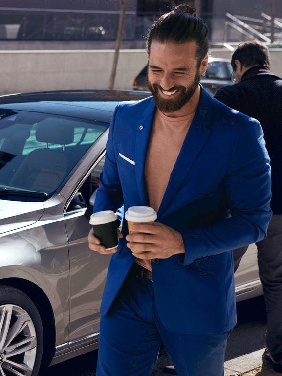 Hombre joven sonriendo con traje azul y dos cafés delaten de un Passat aparcado en la ciudad