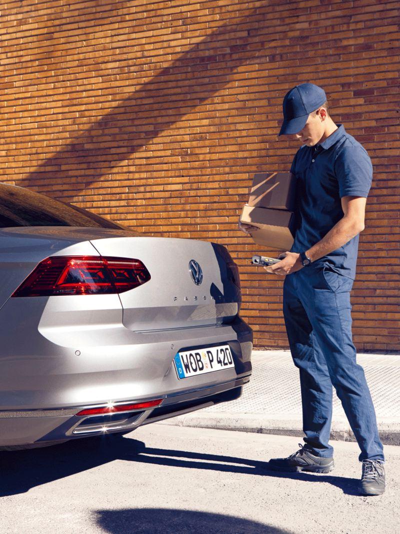 Mensajero vestido de azul dejando paquetes en el maletero de un Volkswagen Passat aparcado en la ciudad