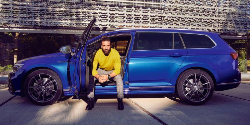 Hombre joven sentado en el puesto del conductor del Volkswagen Passat Variant con la puerta abierta