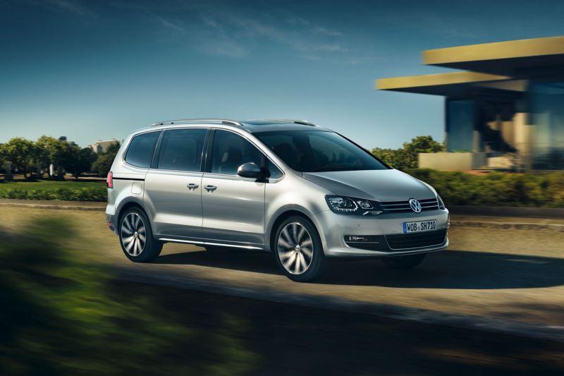 Volkswagen Sharan color plata circulando delante de una casa