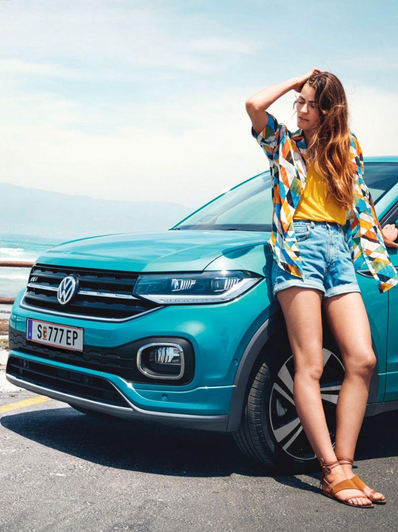 Chica atusándose el pelo apoyada T-Cross azul turquesa aparcado junto a la playa
