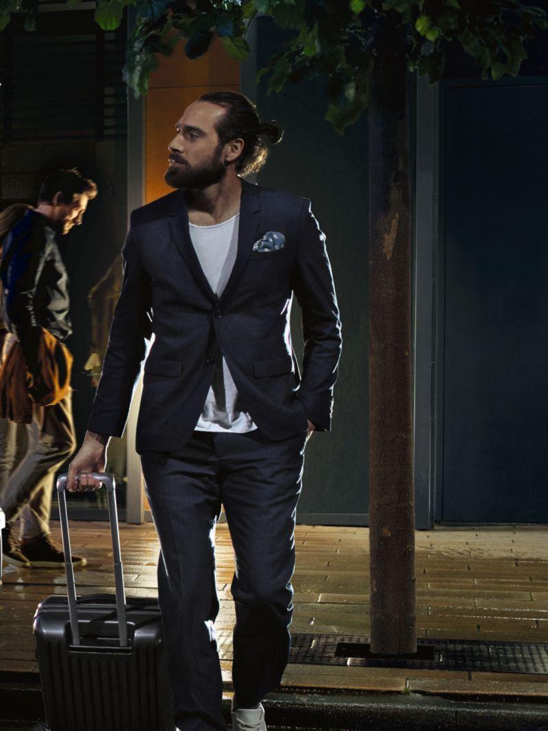 Chico joven caminando por la ciudad en la noche arrastrando una maleta