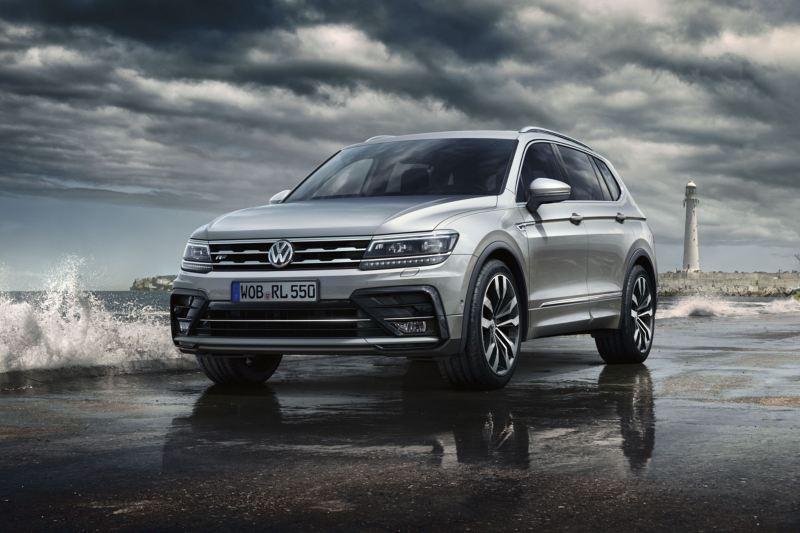 Volkswagen Tiguan Allspace gris aparcado frente a un rompeolas con un faro de fondo