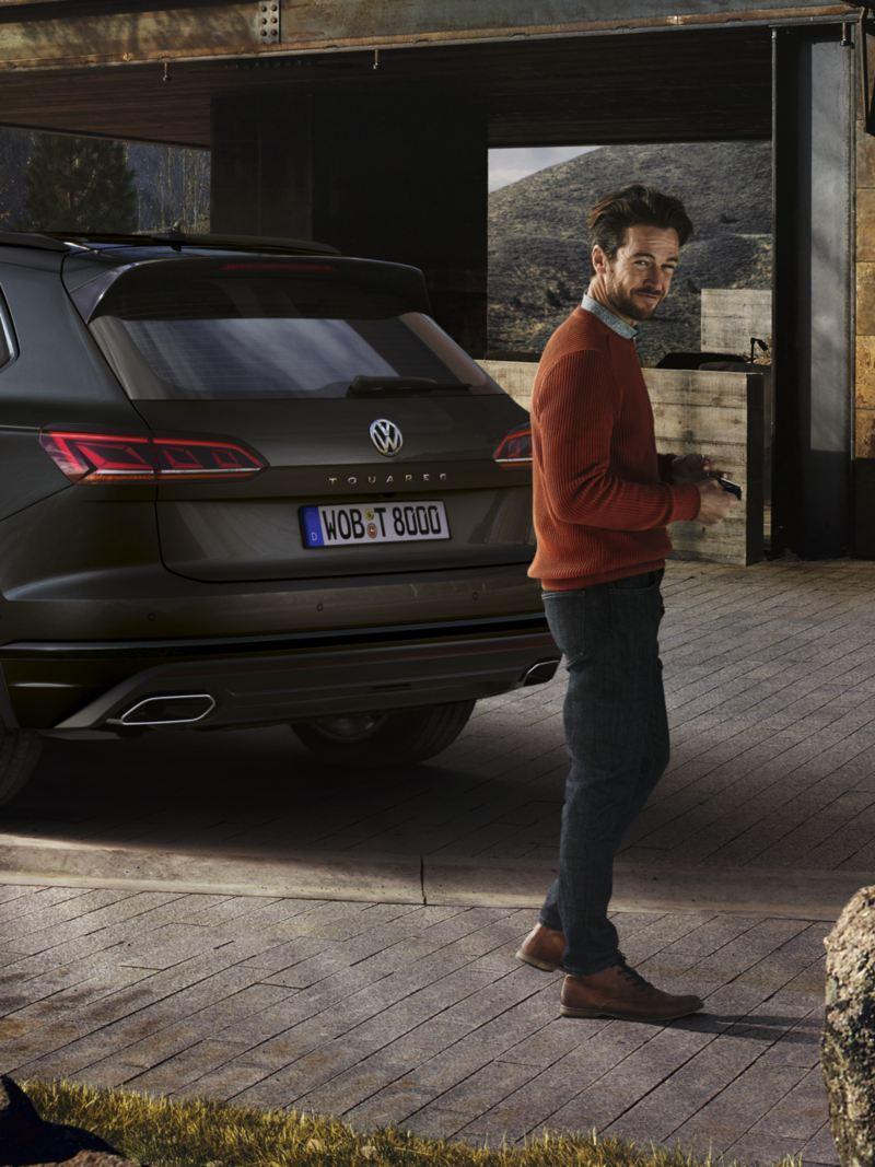 Vista posterior de un Volkswagen Touareg con un hombre joven caminando delante