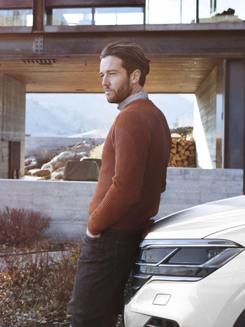 Hombre joven apoyado en el capó de un Volkswagen Touareg