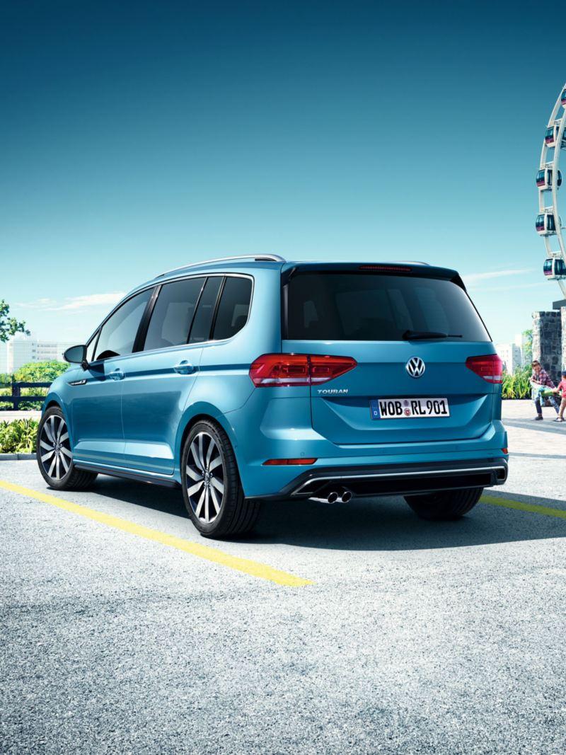Vista trasera de un Touran azul aparcado en una plaza de aparcamiento junto a una noria