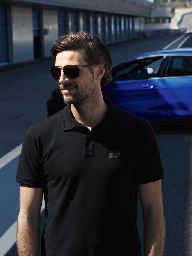 Hombre andando sonriente con unas gafas de sol dejando atrás un Golf R azul