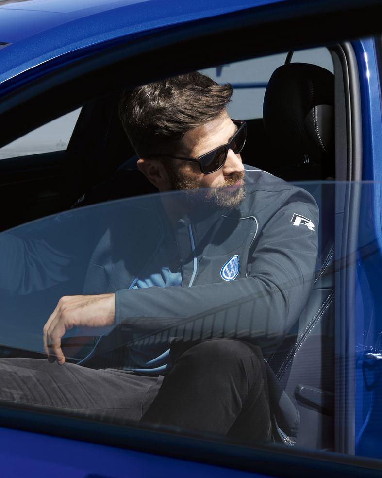 Hombre con gafas de sol sentado en el asiento del conductor de un Golf R azul con la puerta abierta