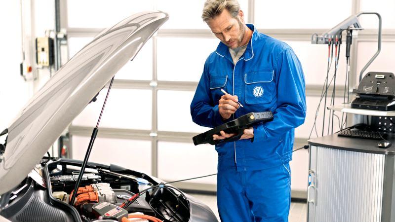 Mecánico con mono azul frente al un Volkswagen con el capó abierto y me motor a la vista