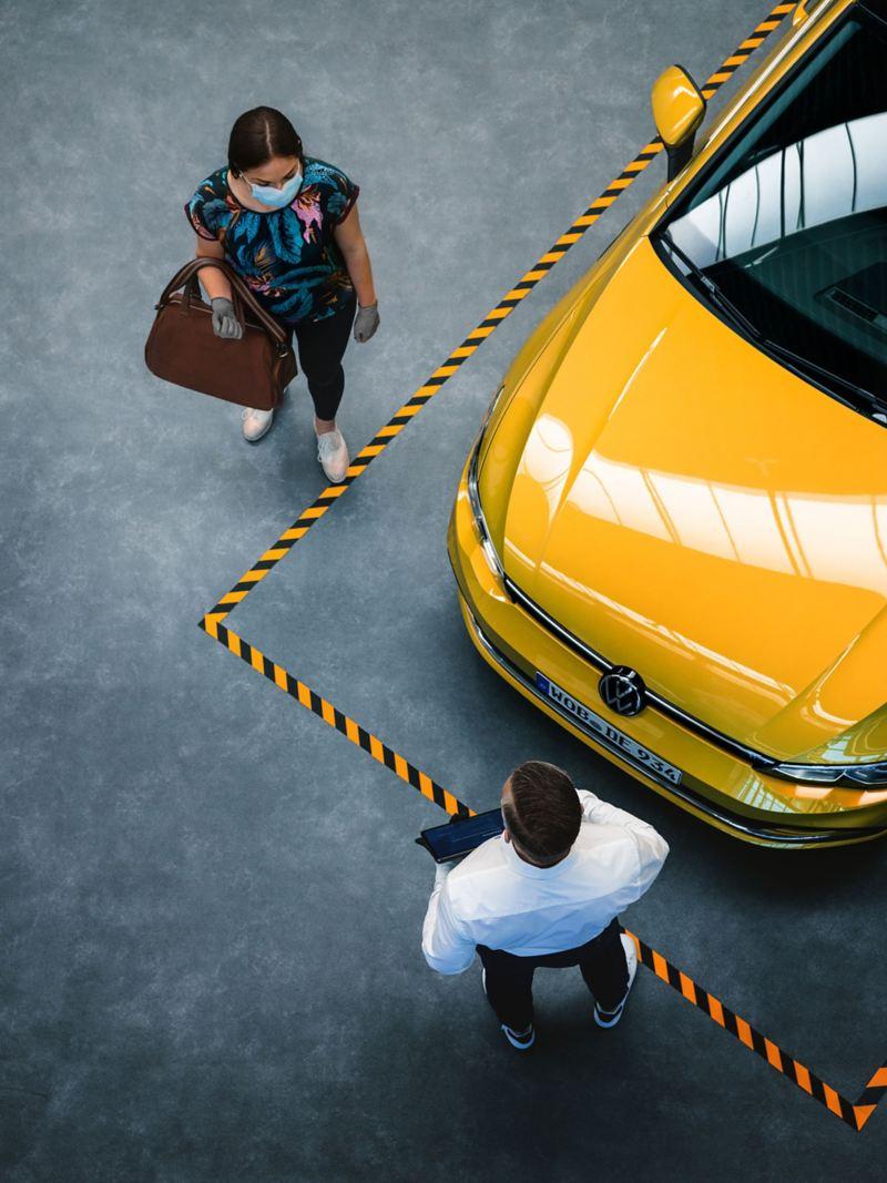Una donna parla con un addetto in un centro Volkswagen Service, al loro fianco un'auto.