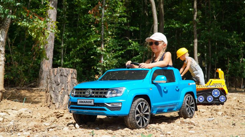 Bambina gioca con mini suv elettrico Volkswagen