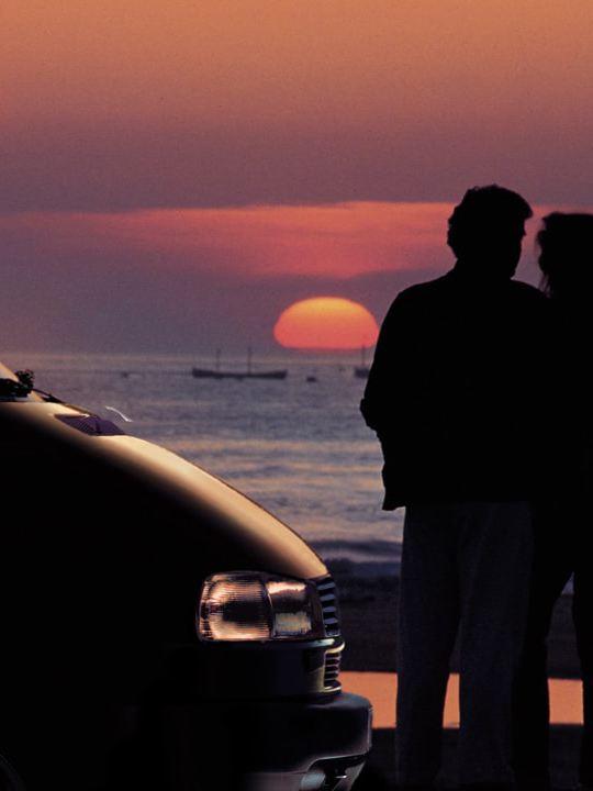Um casal a observar o pôr do sol na praia com a sua California da Volkswagen Veículos Comerciais.