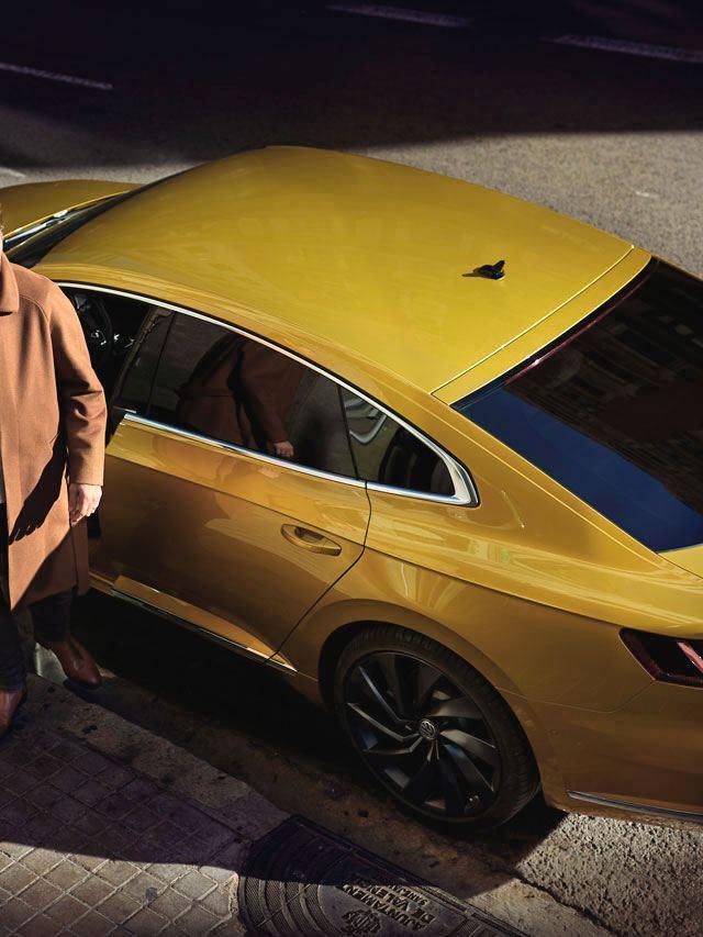 Hombre joven bajando de un Volkswagen Arteon aparcado