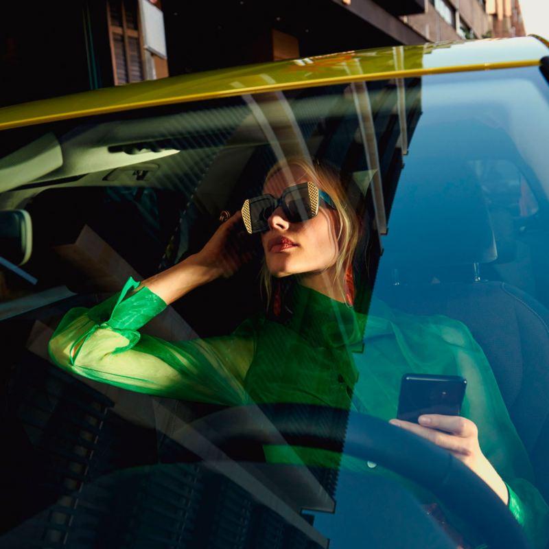 Mujer sentada al volante de un Gol amarillo con un móvil en la mano