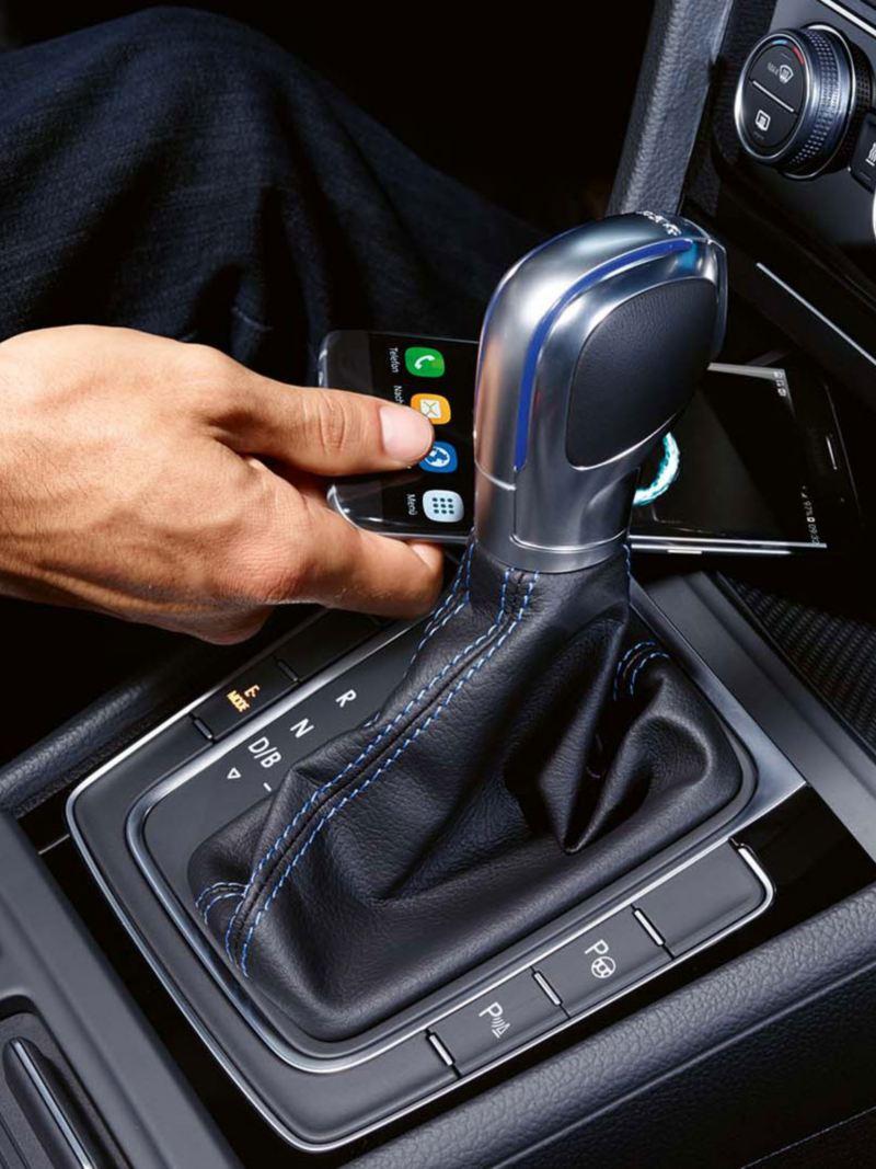 Mano dejando un móvil en el soporte de un Golf GTE