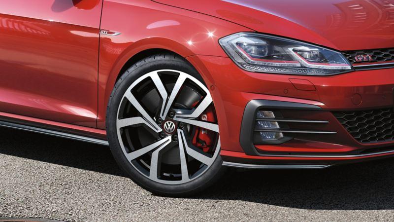 Faros y llantas de un Golf GTI rojo aparcado sobre el asfalto