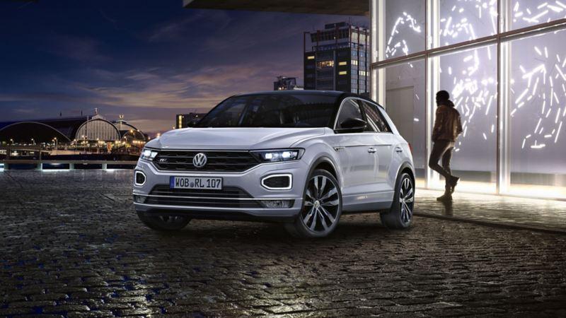 Volkswagen T-Roc blanco aparcado en la ciudad de noche al fondo y un hombre joven caminando por detar