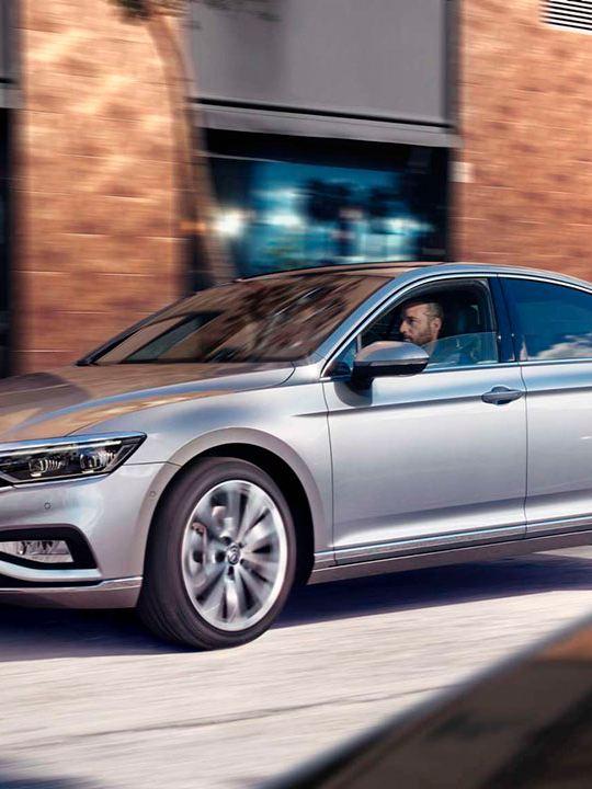 Volkswagen Passat gris visto de costado circulando por la ciudad