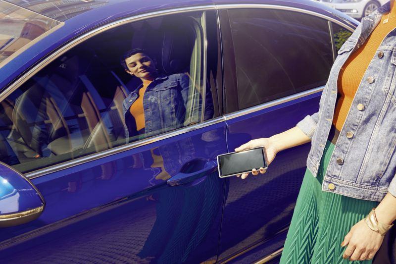 Mujer joven reflejada en la ventana de un Passat azul abriéndolo con el móvil