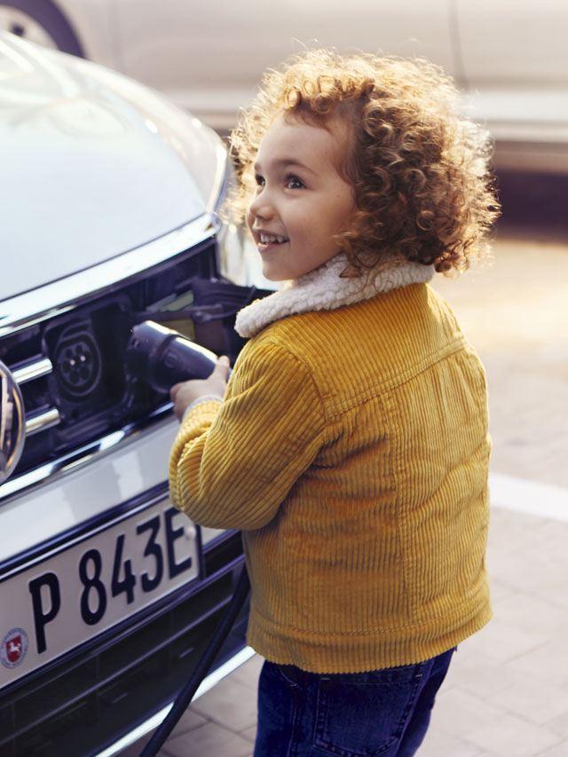 Niña cargando un Volkswagen GTE