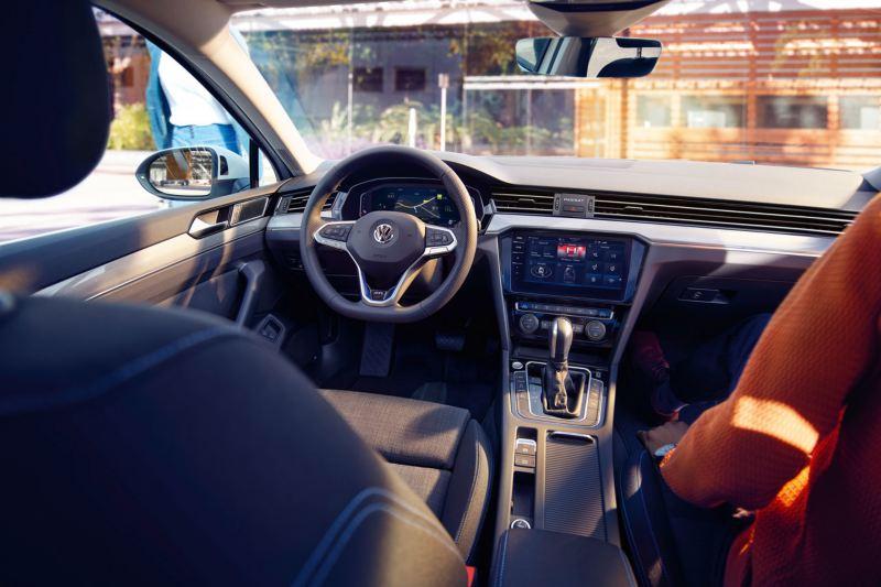 Puesto de conducción del Volkswagen Passat Variant, se ve a un hombre caminando hacia el coche