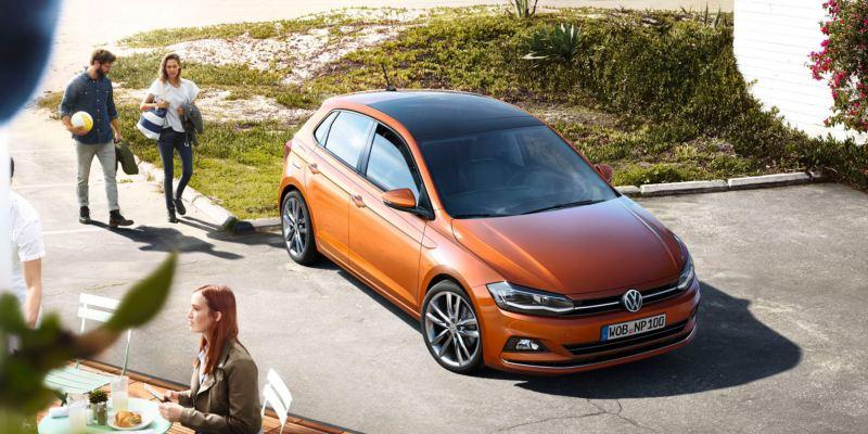 Pareja hablando en dirección a un Volkswagen Polo naranja aparcado