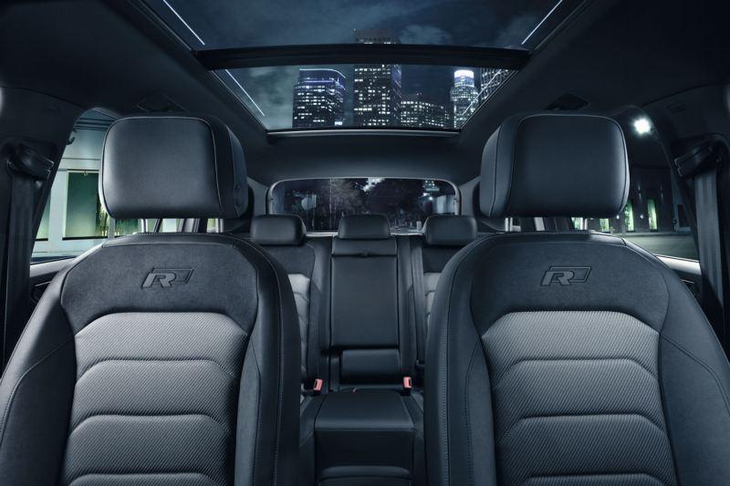 Vista interior de los asientos y el techo solar panorámico de un Volkswagen Tiguan de noche en la ciudad