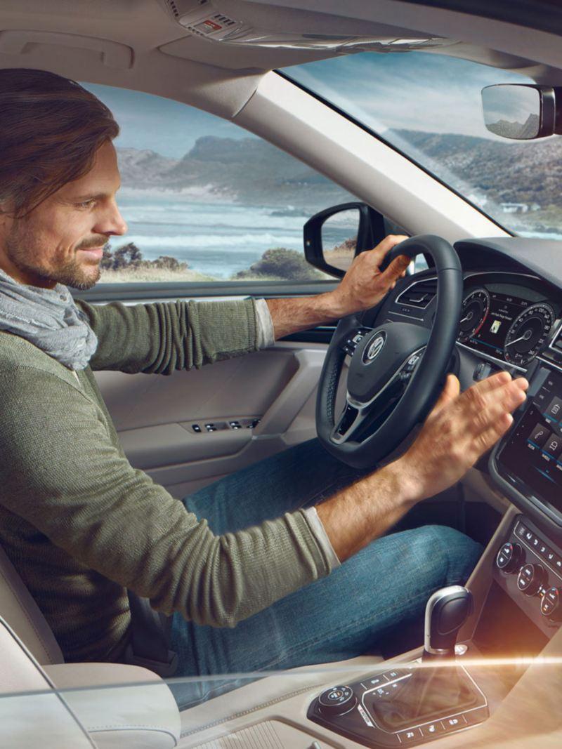 Hombre joven al volante de un Tiguan Allspace usando el control gestual de la pantalla