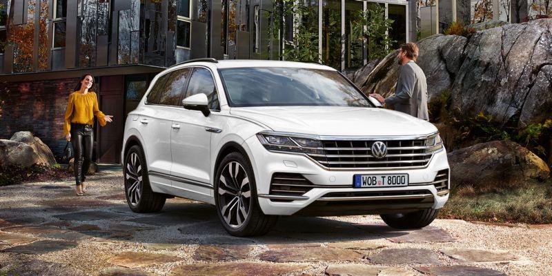 Pareja con el Volkswagen Touareg en la entrada de una casa