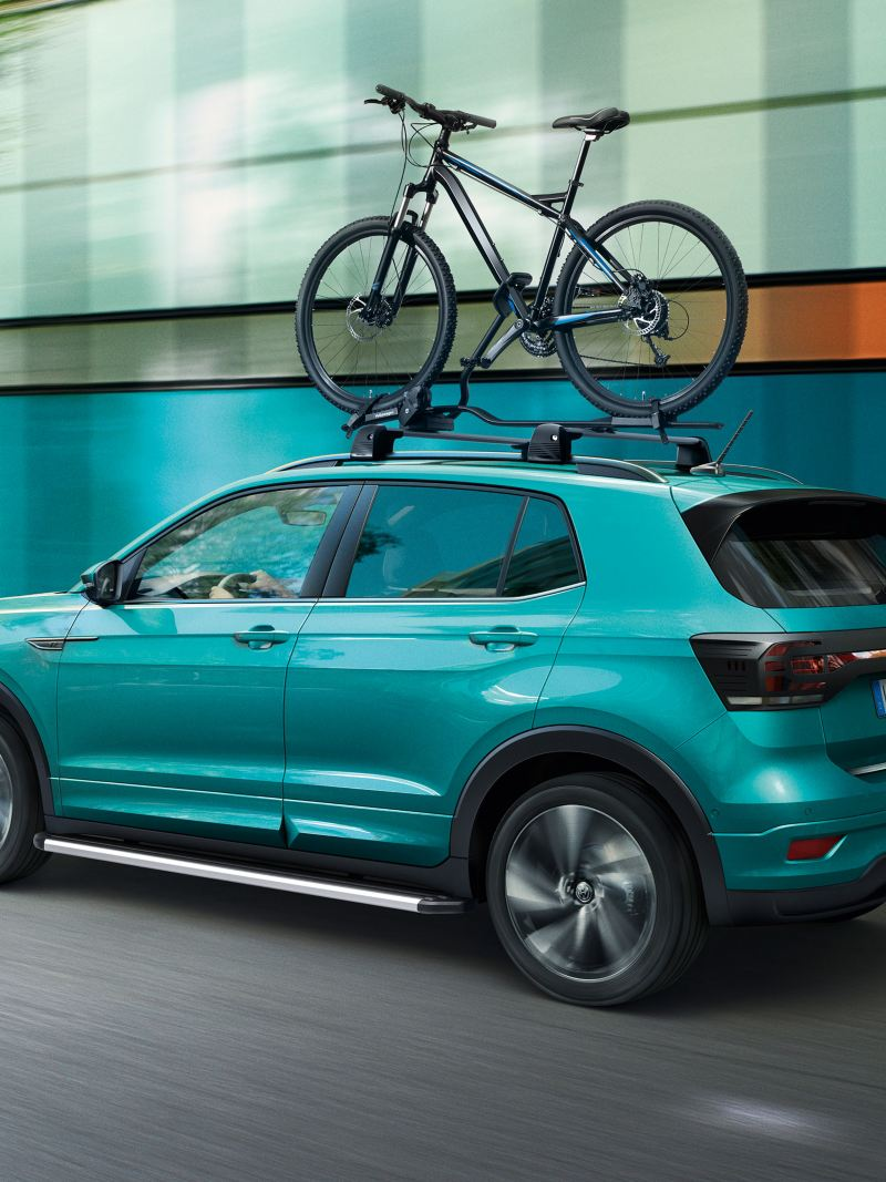 A turquoise VW T-Roc with VW accessories bike rack drives on the road