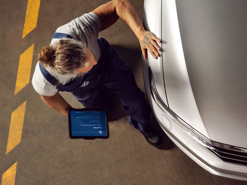 A VW service employee checks a Volkswagen car in the workshop