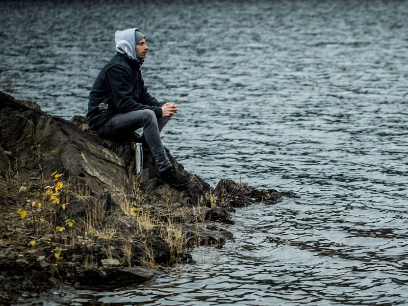 Christian Junker sits at a lake and prepares himself mentally for an excursion