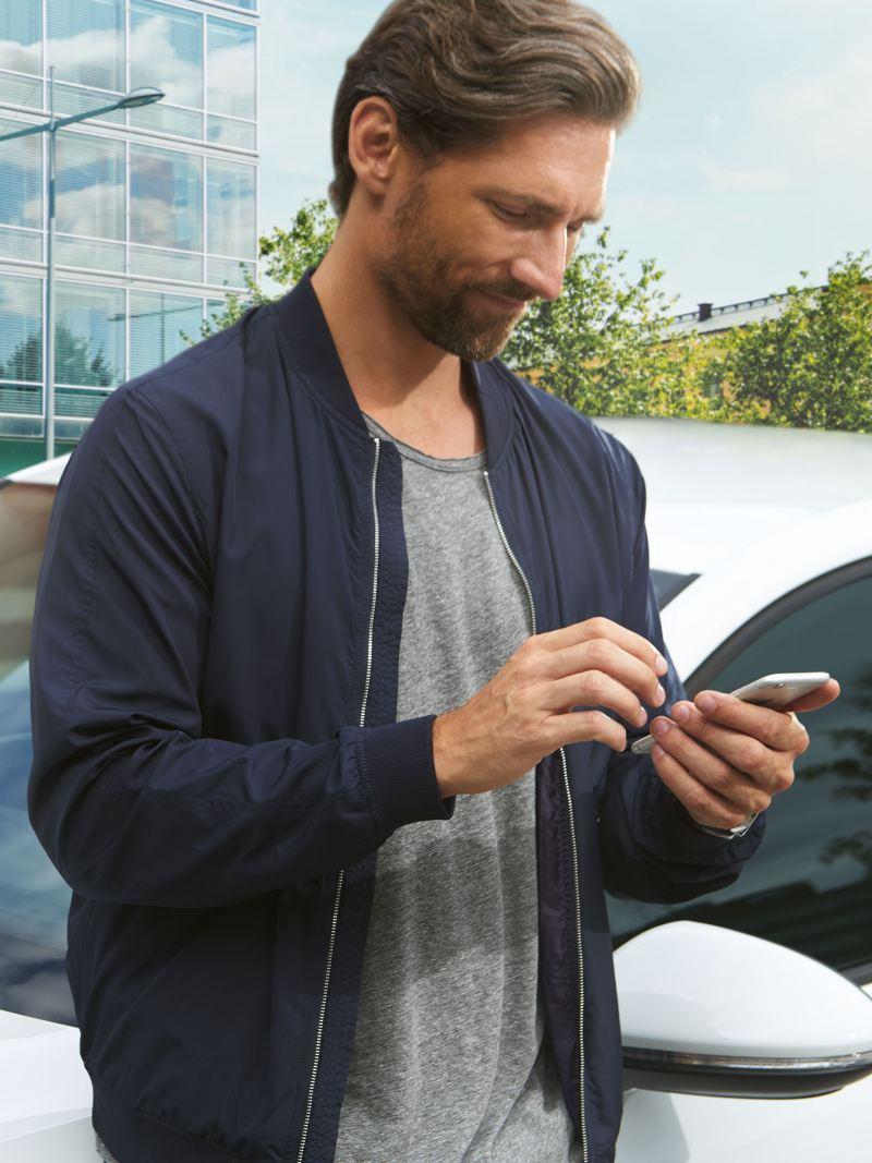 Ein Mann steht mit seinem Smartphone vor seinem weißen e-Golf – VW Notdienst