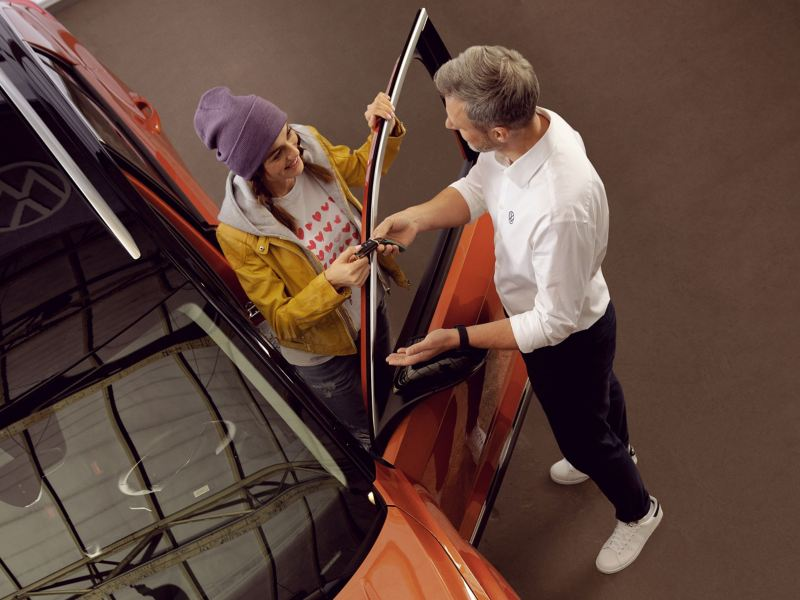 A VW service employee is handing a customer the key to their Volkswagen – VW service