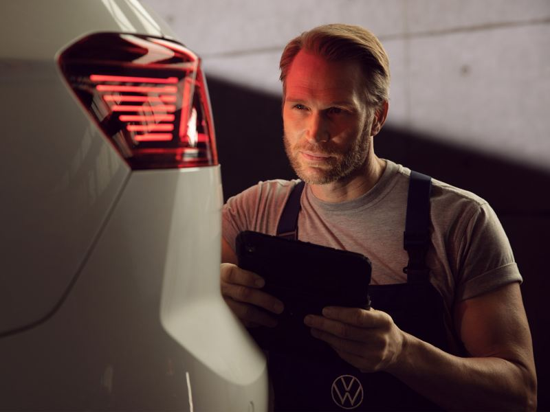 A VW service employee during an inspection of an electric car – service intervals for your model