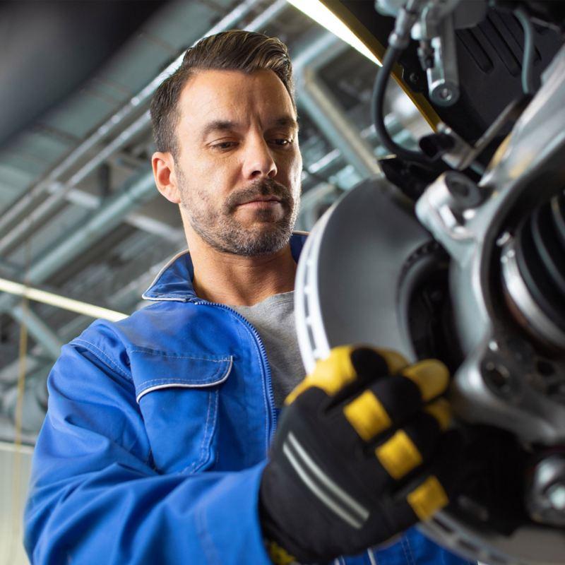 Ein VW Servicemitarbeiter tauscht eine Bremsscheibe aus: unsere Volkswagen Original Teile®