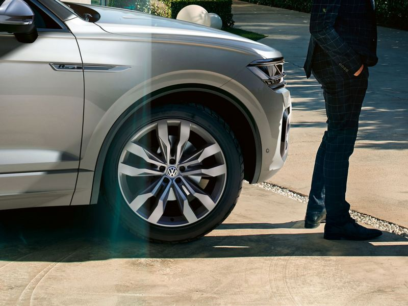 A man is standing in front of a silver VW car with summer tyres