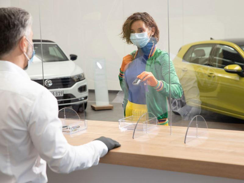 Una donna consegna le chiavi dell'auto ad un addetto presso un centro Volkswagen Service.