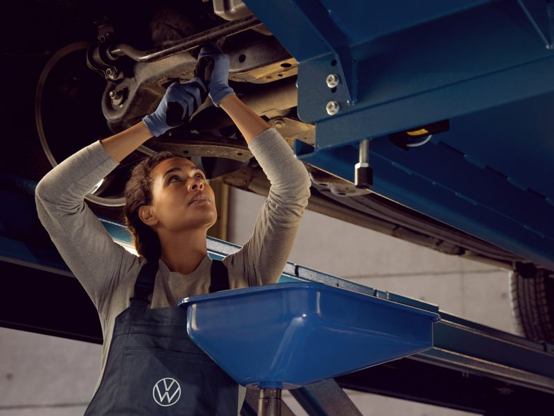A VW service employee during an inspection with an oil change